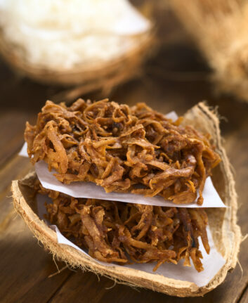 Peruvian cocadas, a traditional coconut dessert sold usually on the streets, made of grated coconut and brown sugar, which gives the coloring of it (Selective Focus, Focus on the front of the cocadas)